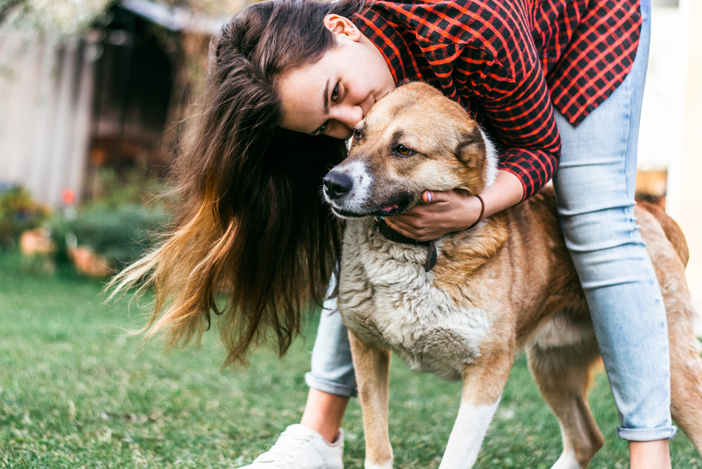Woman in Los Angeles cuddles dog on artificial grass